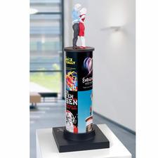 """Die 43 cm hohe Skulptur zeigt – neben Plakatwerbungen für ein Rockkonzert, eine Museumsausstellung und ein Klassikensemble – Fotografien von zwei """"Säulenheiligen""""."""