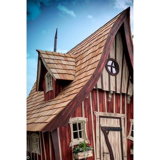 """Einfach zum Verlieben: die Holzbauweise des Hauses mit vielen schönen Details. """"Windschiefe"""" Gauben lugen aus dem Dach. Ein zentrales Rundfenster, Sprossenfenster und eine antik anmutende Tür geben der Front das märchenhafte Gesicht."""